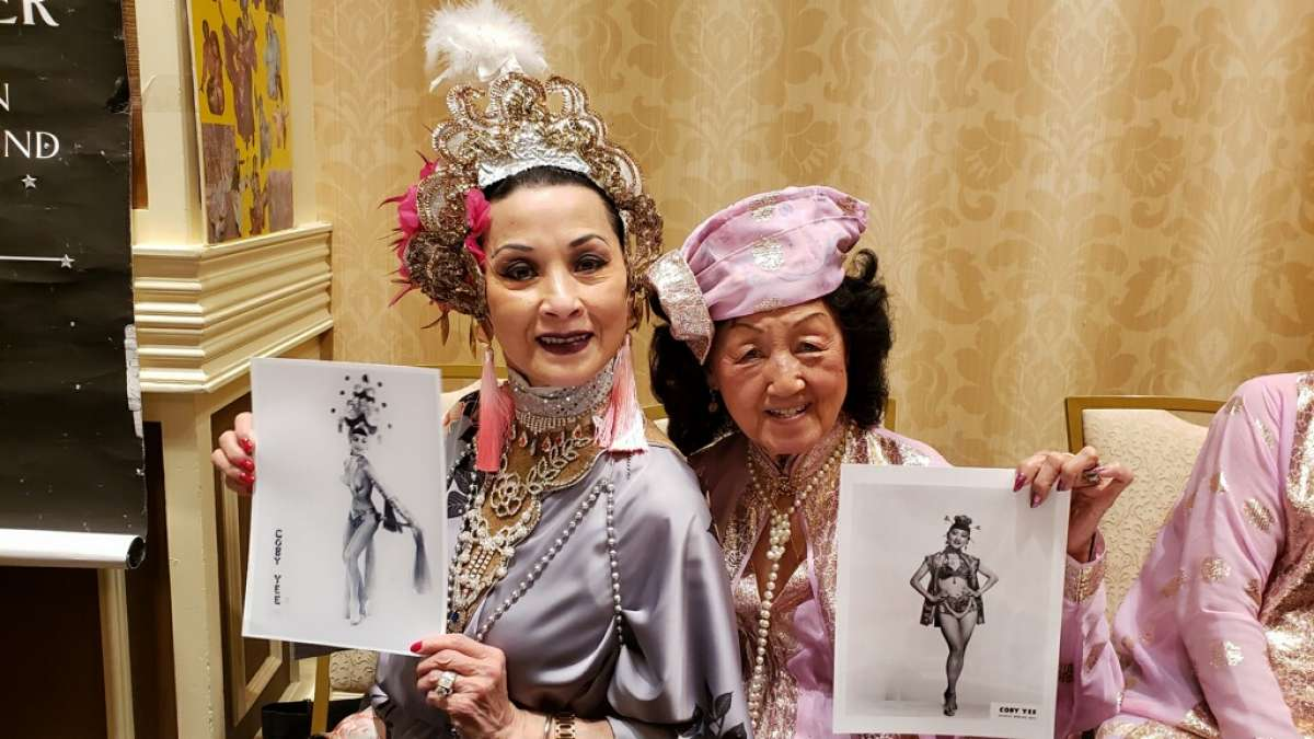 Coby Yee, right,gives one of her handcrafted headdresses to Patricia Chin, a member of the Grant Avenue Follies, at the Burlesque Hall of Fame in Las Vegas.